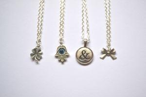 L-R: Lucky Clover bracelet, Hamsa Evil Eye necklace, Ampersand necklace, Dainty Bow bracelet